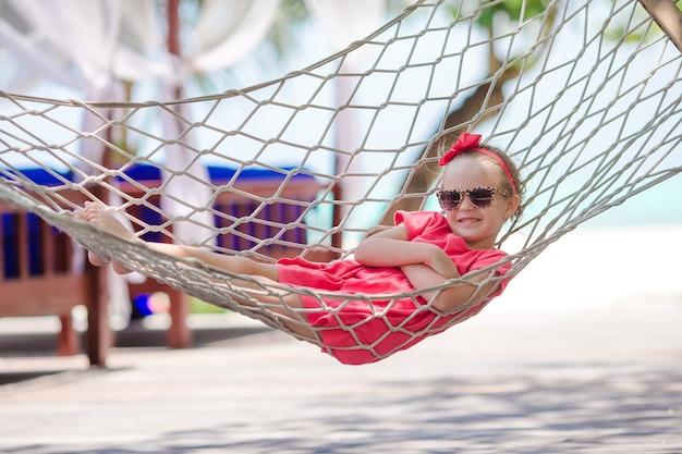 Adorable niña en vacaciones tropicales relajantes en hamaca