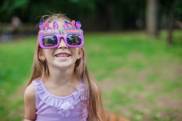 Adorable niña en vasos de feliz cumpleaños sonriendo al aire libre