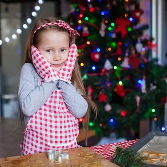 Adorable niña vestida con guantes para hornear galletas de jengibre de navidad