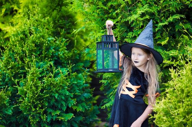 Adorable niña vestida con traje de bruja con escoba en halloween al aire libre