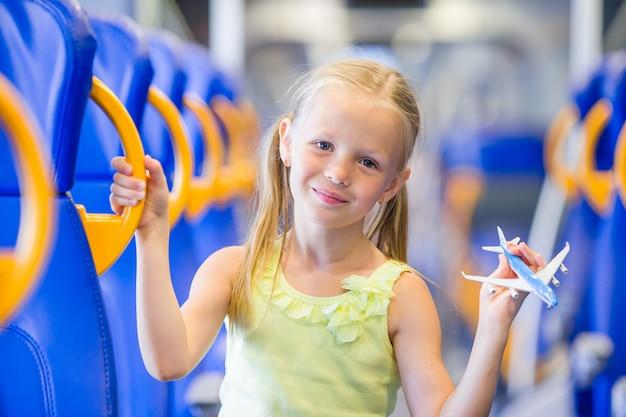 Adorable niña viajando en tren y divirtiéndose con modelo de avión en manos