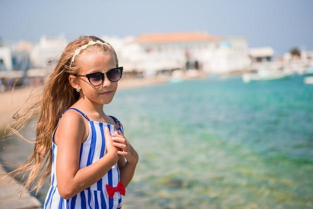 Adorable niña en la vieja calle del típico pueblo tradicional griego