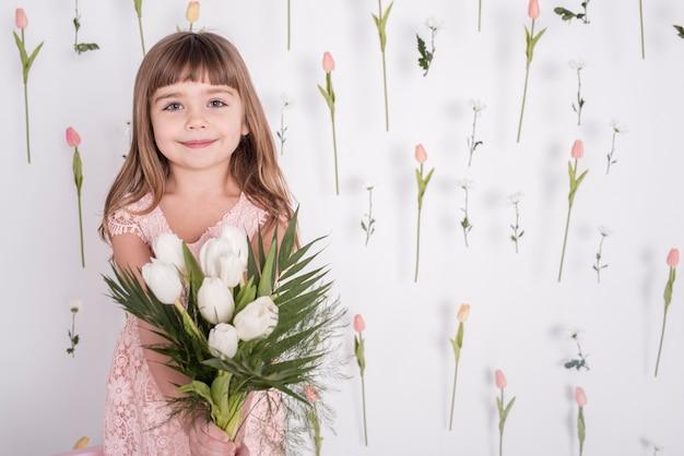Adorable niña con vista frontal de tulipanes