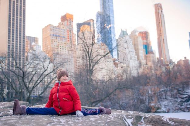 Adorable niña con vista de pista de hielo en central park en la ciudad de nueva york