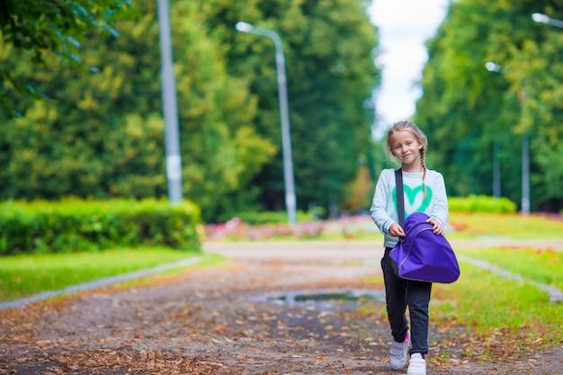 Adorable niña yendo al gimnasio con su bolsa de deporte