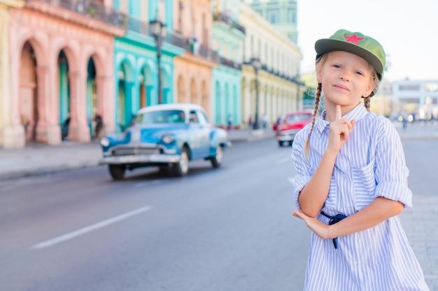 Adorable niña en zona popular en la habana vieja, cuba. retrato de niño, vintage clásico coche americano