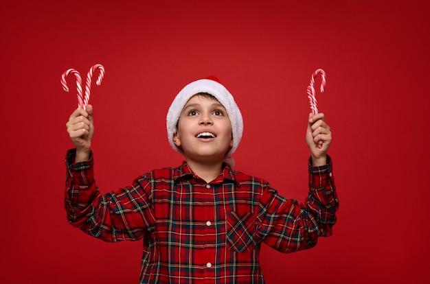 Adorable niño de 9 años con gorro de papá noel tiene dulces paletas de navidad a rayas, bastones de caramelo en las manos y sonríe tiernamente con una hermosa sonrisa con dientes, mirando en el espacio de la copia sobre un fondo rojo.