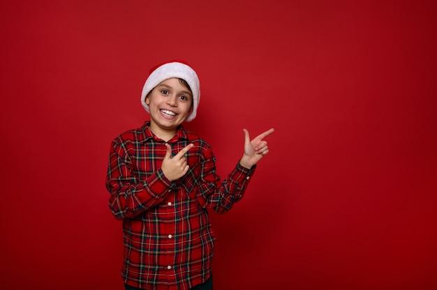 Adorable niño alegre preadolescente europeo, niño guapo con sombrero de santa y puntos de camisa a cuadros con los dedos en un espacio de copia sobre fondo de color rojo para publicidad de navidad y año nuevo