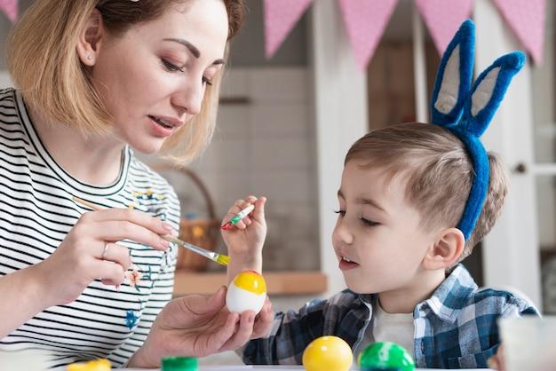Adorable niño aprendiendo a pintar huevos para pascua