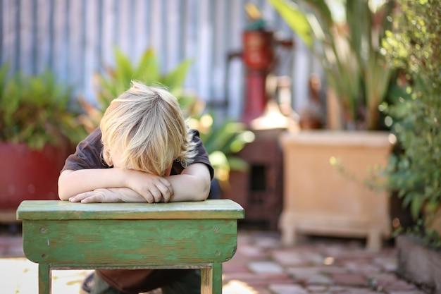 Adorable niño australiano rubio sentado y apoyado en una pequeña mesa de la escuela en el patio de la casa