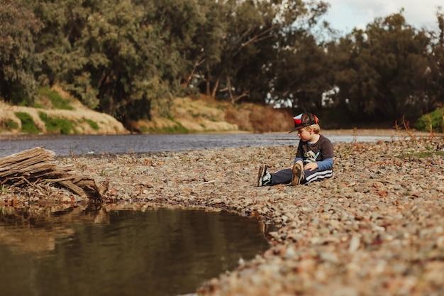 Adorable niño australiano rubio sentado sobre guijarros en la orilla del río
