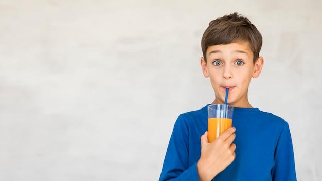 Adorable niño bebiendo un poco de jugo de naranja