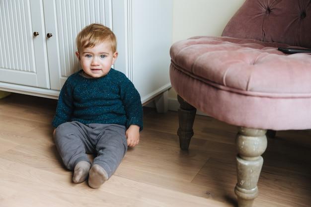 Adorable niño con encantadores ojos azules y cabello rubio, se sienta en el piso contra el interior de la casa