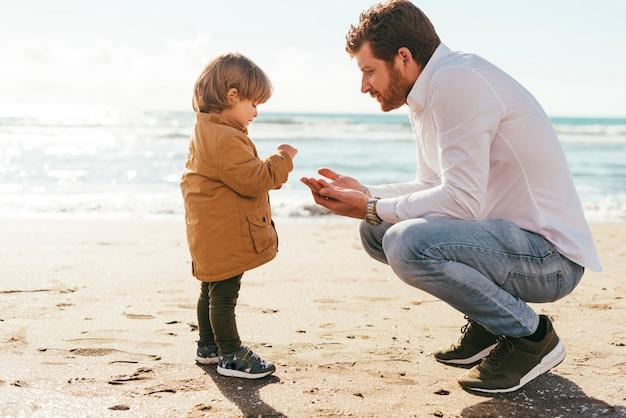 Adorable niño familiarizándose con la arena de la playa