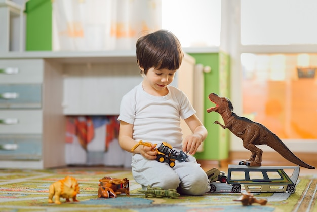 Adorable niño jugando con dinosaurios alrededor de muchos juguetes en casa