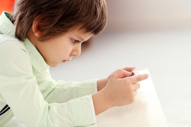 Adorable niño jugando con un teléfono inteligente