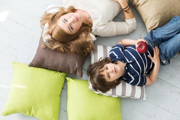 Adorable niño con madre comiendo manzana