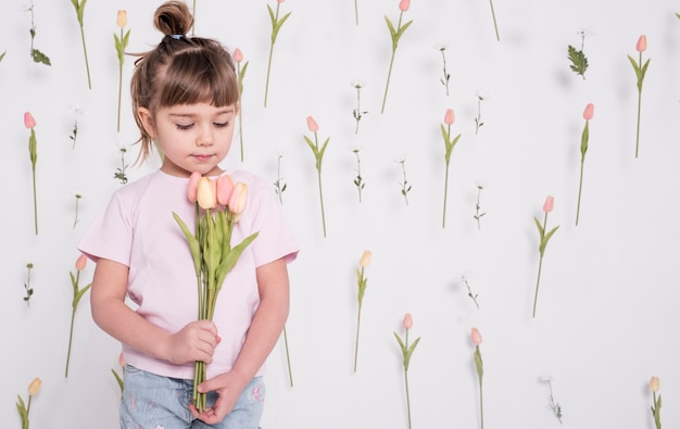 Adorable niño mirando tulipanes