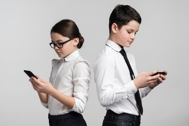 Adorable niño y niña enviando mensajes de texto en teléfonos móviles