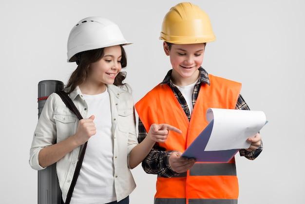Adorable niño y niña leyendo el plan de construcción