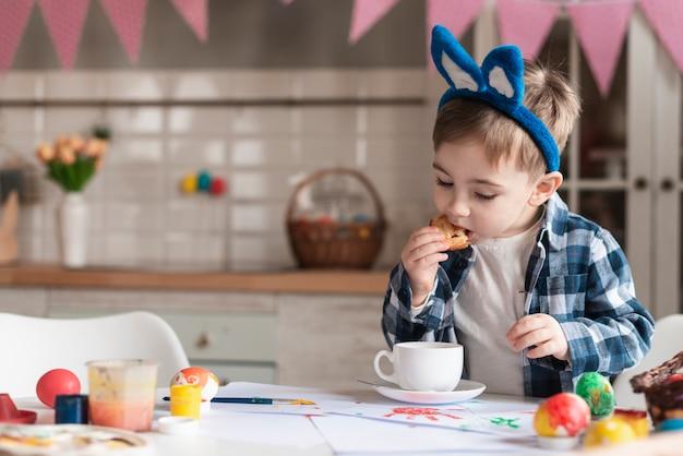Adorable niño con orejas de conejo comiendo una galleta