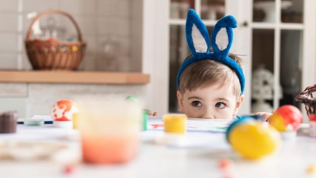 Adorable niño con orejas de conejo escondido
