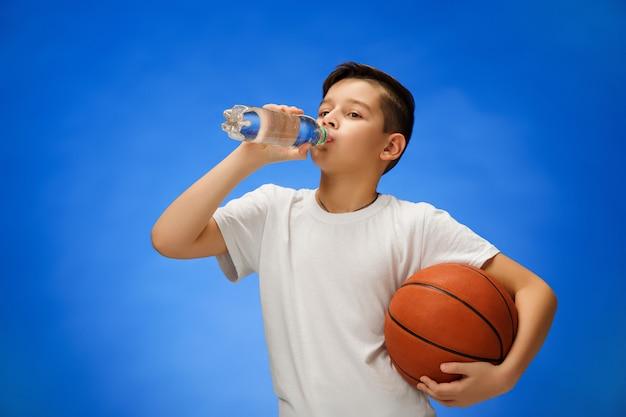 Adorable niño con pelota de baloncesto