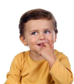 Adorable niño pequeño de dos años chupando su mano aislado en un fondo blanco