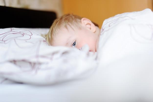 Adorable niño pequeño durmiendo en una cama