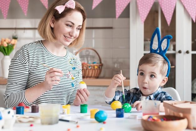 Adorable niño pintando huevos de pascua con madre