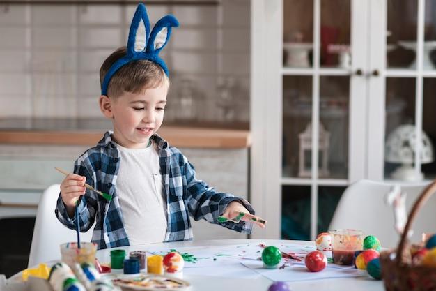 Adorable niño pintando huevos para pascua
