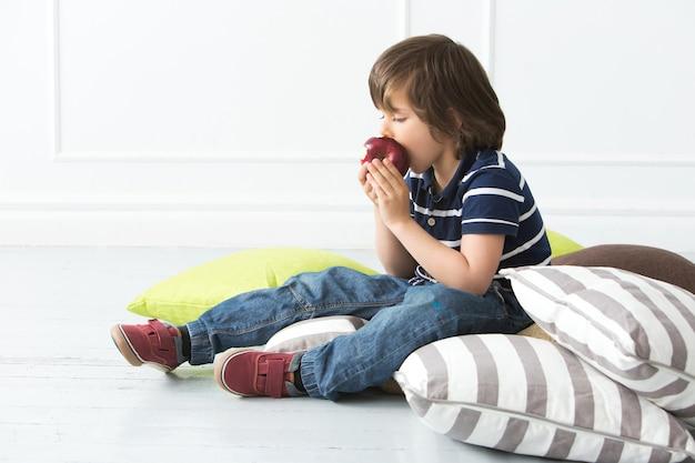Adorable niño en el piso comiendo manzana