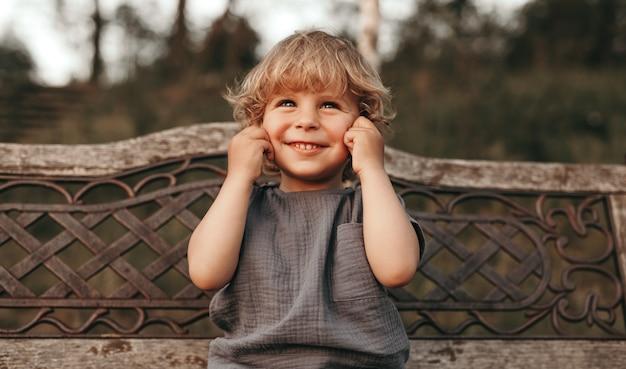 Adorable niño rubio sonriendo y pellizcando las mejillas