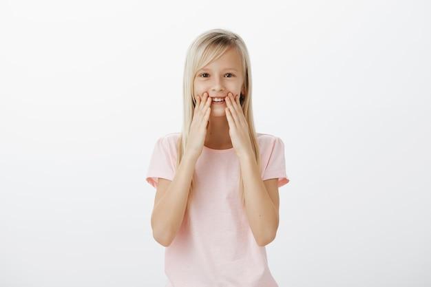Adorable niño sonriendo, reacciona impresionado y feliz