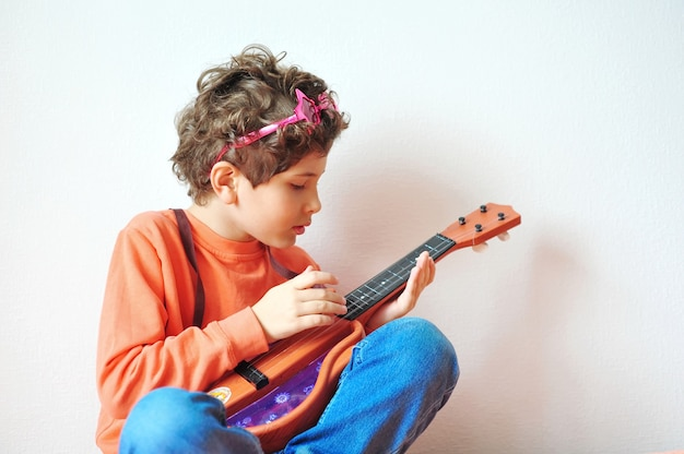 Adorable niño tocando rock and roll en una guitarra de juguete