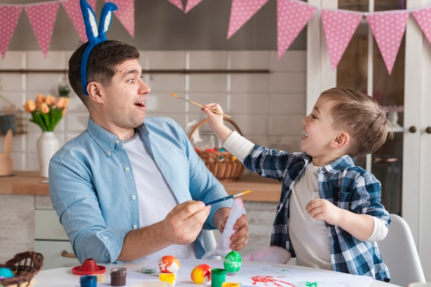Adorable niño tratando de pintar a su padre