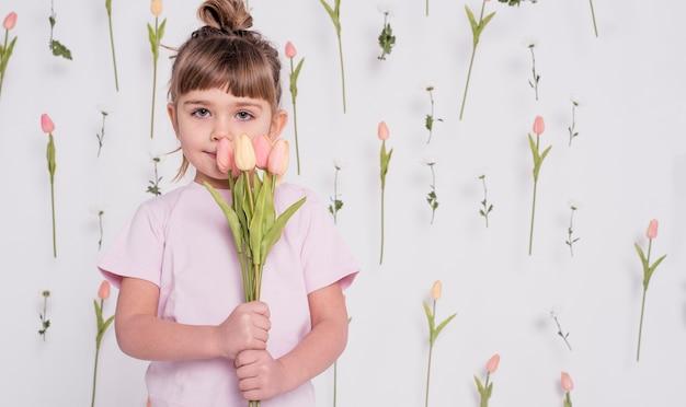 Adorable niño con tulipanes tiro medio