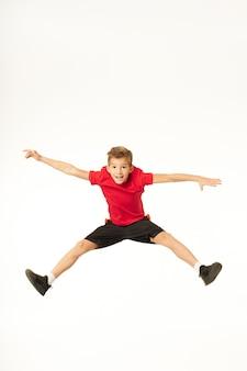Adorable niño varón en pantalones cortos extendiendo las manos a los lados y saltando mientras mira a la cámara y sonríe. aislado sobre fondo blanco