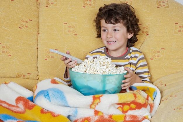 Adorable niño viendo la tele en su casa.