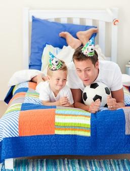 Adorable niño y su padre jugando con un balón de fútbol
