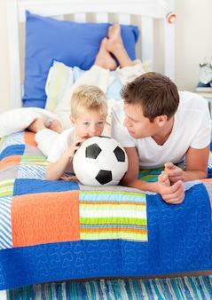 Adorable niño y su padre viendo un partido de fútbol