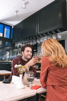Adorable pareja bebiendo vino y conversando