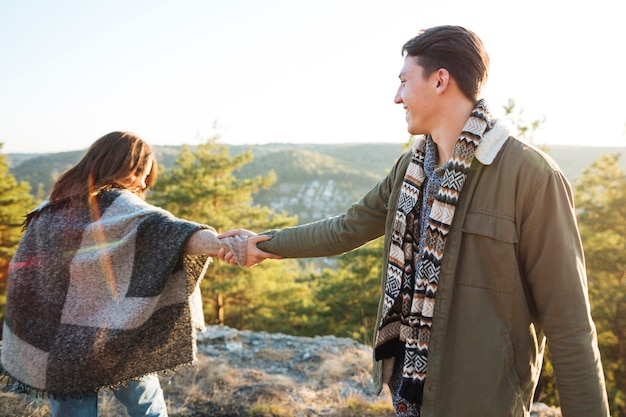 Adorable pareja cogidos de la mano al aire libre