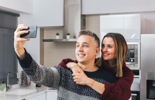 Adorable pareja joven sonriendo y tomando un selfie con teléfono móvil en casa