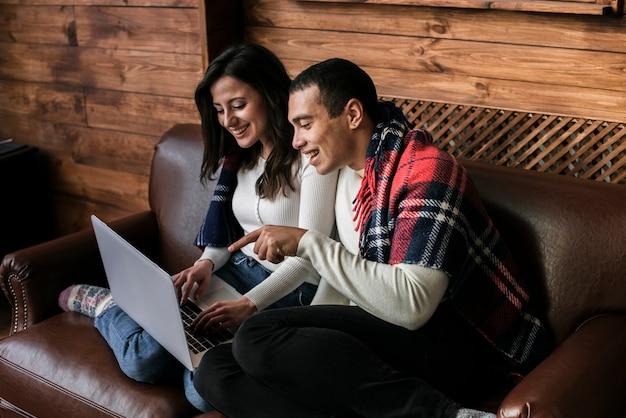 Adorable pareja junto con una computadora portátil
