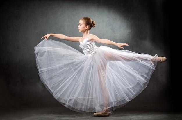 Adorable pequeña bailarina bailando en estudio. la niña está estudiando ballet.
