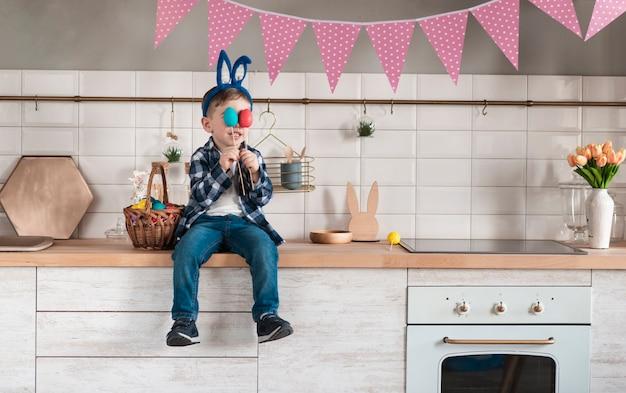 Adorable pequeño jugando con huevos de pascua