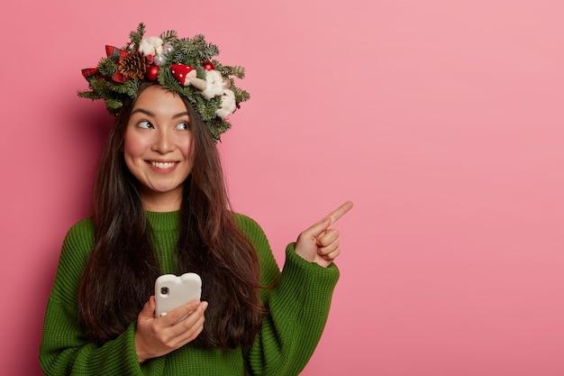 Adorable señorita sonríe agradablemente vistiendo una corona festiva en la cabeza
