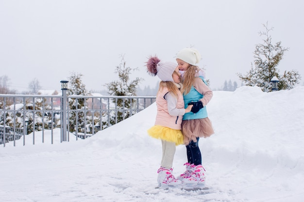 Adorables chicas patinando en la pista de hielo al aire libre en invierno día de nieve