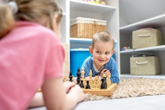Adorables hermanos tendidos en el suelo y jugando al ajedrez entre sí